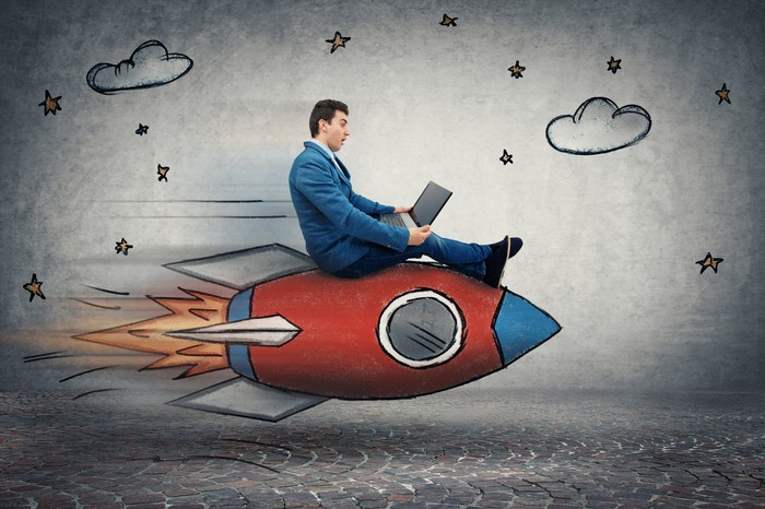 A businessman rides a rocket ship while looking at a laptop computer.