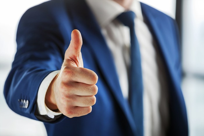 A man in a business suit pointing his thumb up