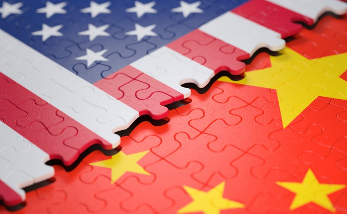 A puzzle painted as the U.S. flag connecting with a puzzle painted as China's flag