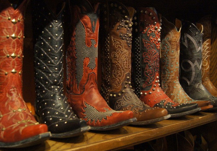 Various cowboy boots lined up on a wooden store shelf.