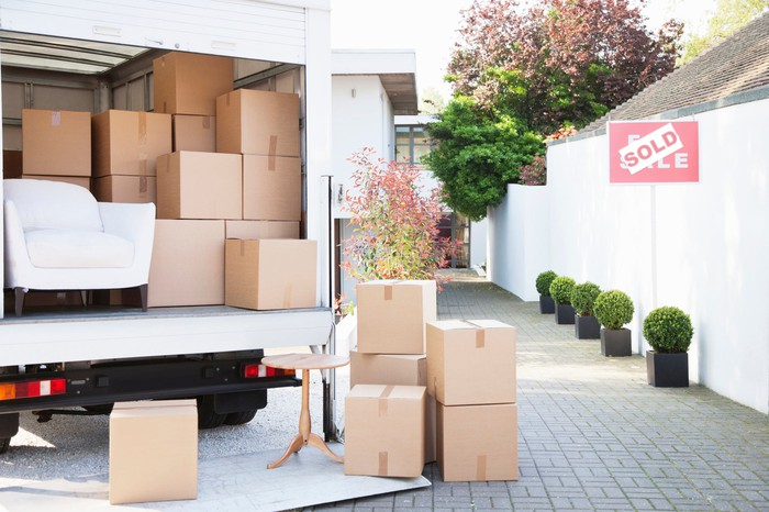 A moving truck, parked on a driveway, packed with boxes and a white club chair.