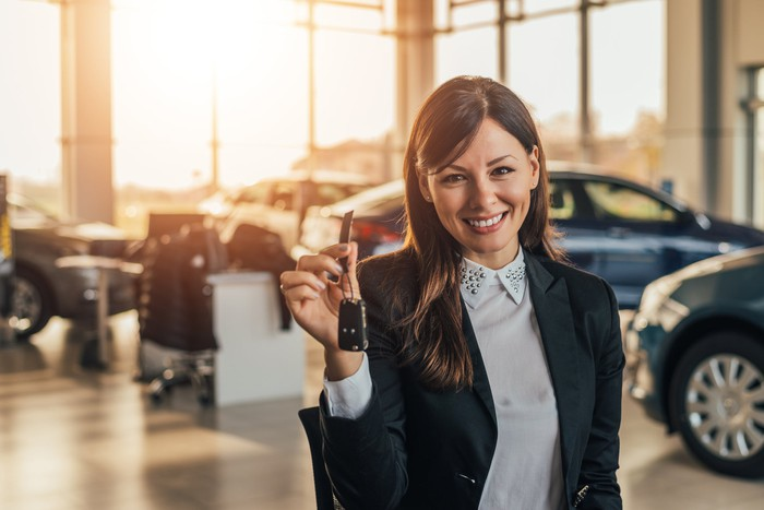 A woman holds up the keys to a new car at a dealership.