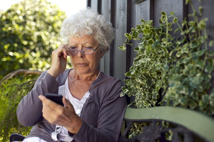 Senior woman sitting on a bench outdoors and adjusting glasses while looking at mobile phone
