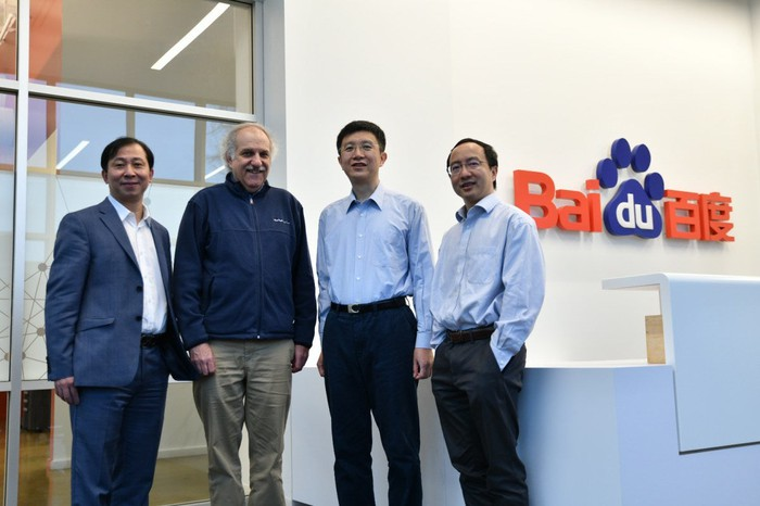 Baidu research executives posing in front of the Baidu front desk with the Baidu logo on the wall behind them.