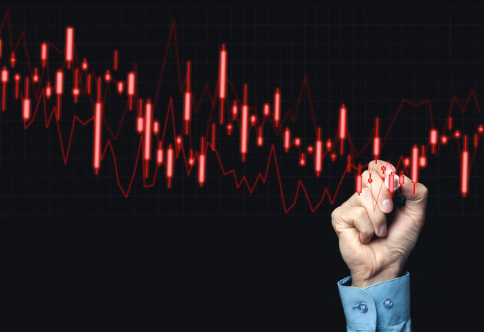 Hand grasping a marker and pointing to a red falling bar chart