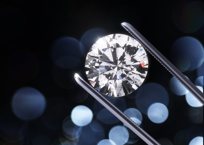A sparkling round-cut diamond held in a jeweler's tweezers.