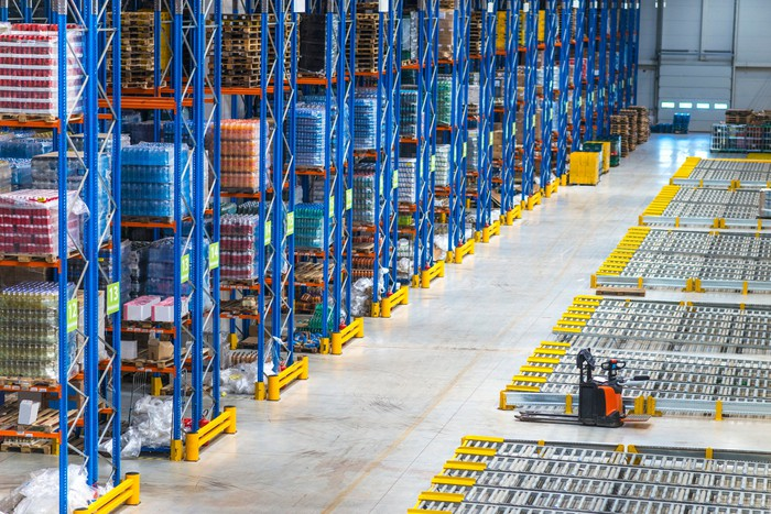 Top view of large storage area in a distribution warehouse interior with goods on the shelf and forklifts