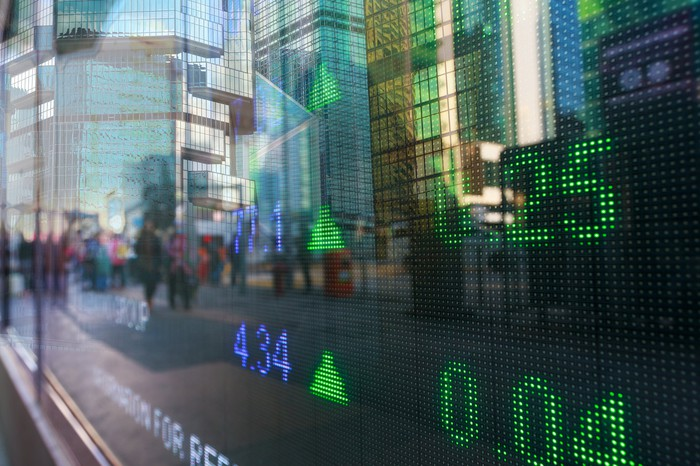 Stock market prices on a digital window display with city reflection on the glass.