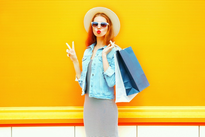 A young female shopper makes a peace sign while carrying shopping bags.