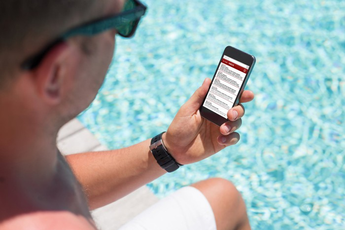 Man sitting by a pool reading text on mobile phone screen