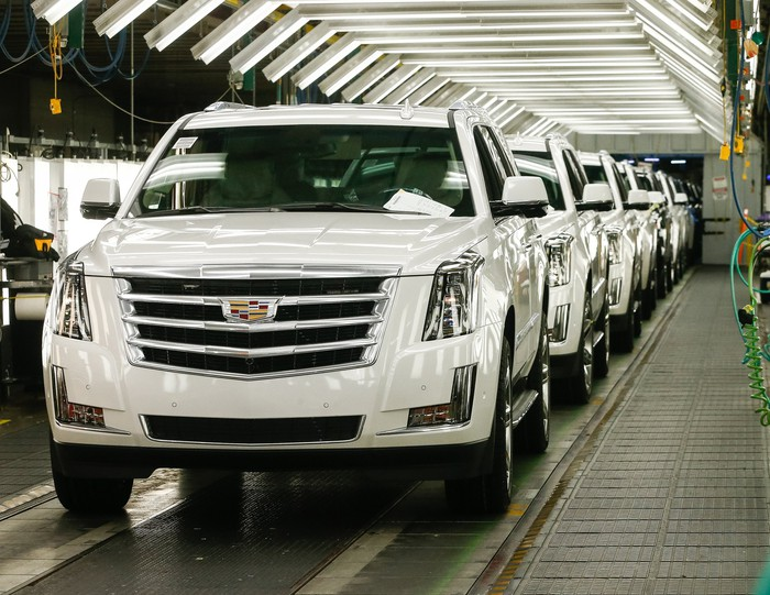 Several Cadillac SUVs coming off the assembly line at a GM plant.