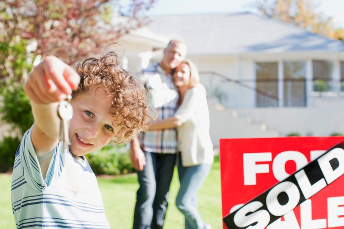 A couple standing in front of a house with a sold sign and a child holding out keys.