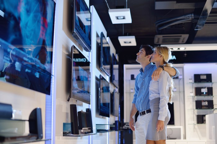 A young man and woman looking at a wall of TVs in a store.