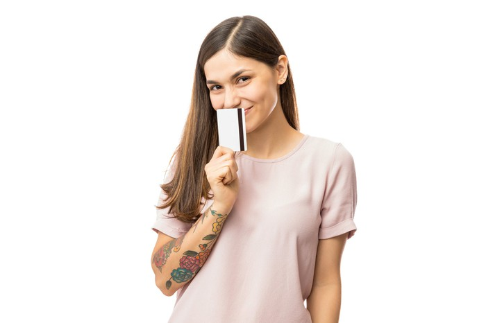 A young woman with a forearm tattoo smiles and holds a credit card to her nose.