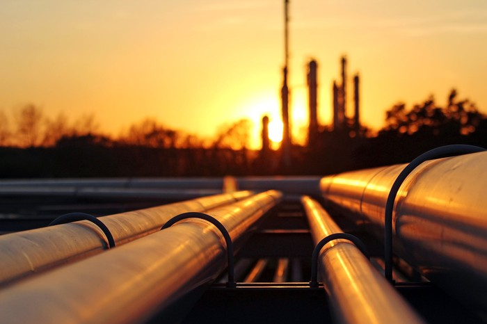 Pipeline pipes with a refinery in silhouette at sunset.
