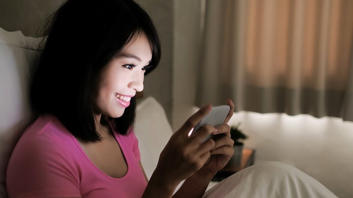 Celebrity Culture: A young woman playing a game on a smartphone.