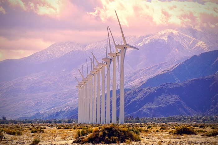 A row of wind turbines in the desert with a mountain in the background.