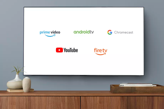 A wall mounted TV showing various logos, including Prime Video, AndroidTV, Chromecast, YouTube and FireTV.