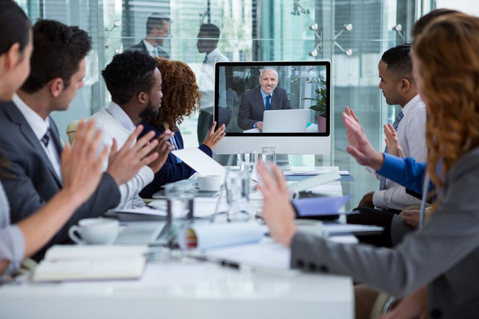 A group of people in an office watching a video monitor.