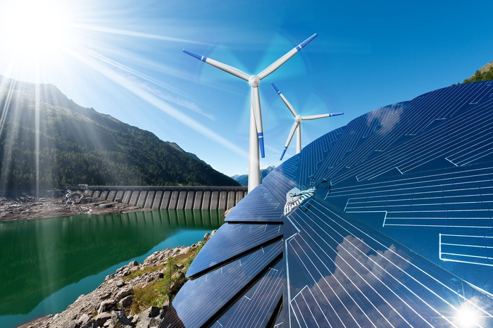 Solar panels and a wind farm next to a dam on a river