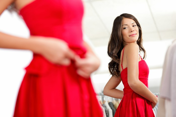 A woman looks at herself in a mirror as she tried on a red dress.