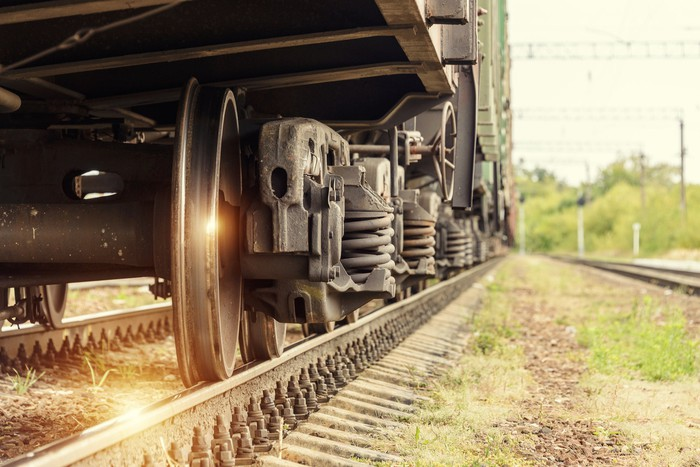 A ray of sunshine reflects off a freight train wheel.
