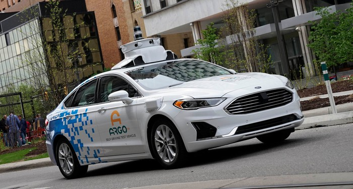 A white Ford Fusion sedan with Argo AI logos and visible self-driving sensor hardware is shown driving on a Detroit city street.