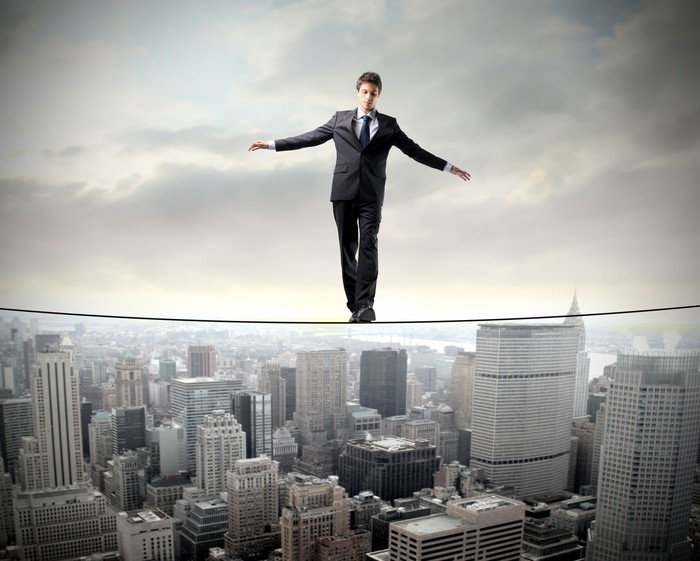 A man in a suit walking a tightrope above a city.