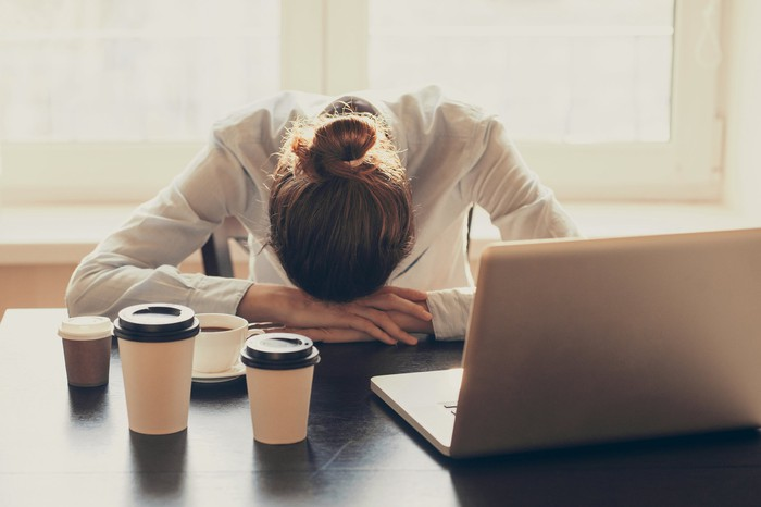 A woman surrounded by coffee cups has her head down on her desk.