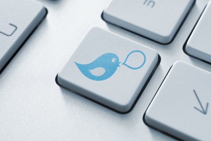 An image of a keyboard with a button of a blue bird and a speech bubble.