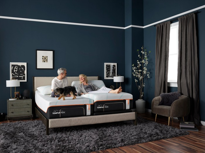 An elderly couple relaxes on a Tempur-Pedic bed.