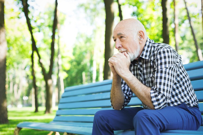Older man sitting on park bench with thoughtful expression