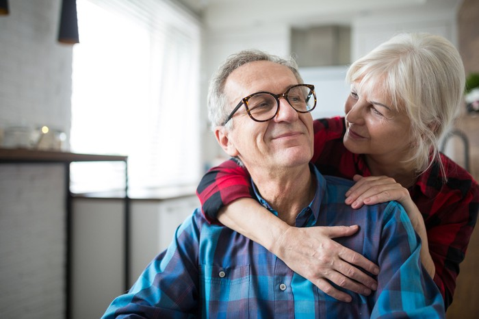 Older woman putting her arms around an older man