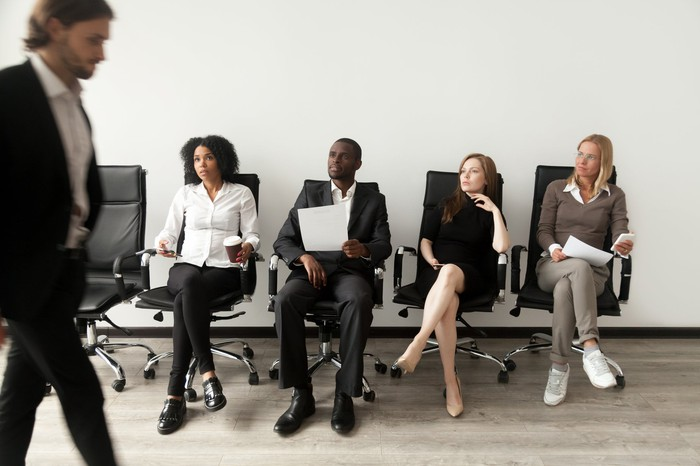 A man walks by four people seated as if waiting for interviews.