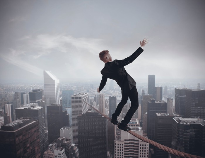Businessman balancing precariously on a wire streatched high above a bustling cityscape.