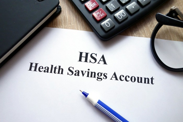 Document labeled HSA with pen sitting on it on wooden surface with notebook, calculator, and glasses