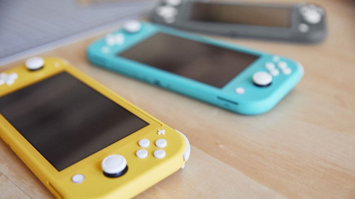 A yellow, blue, and grey Switch Lite laying on a table.