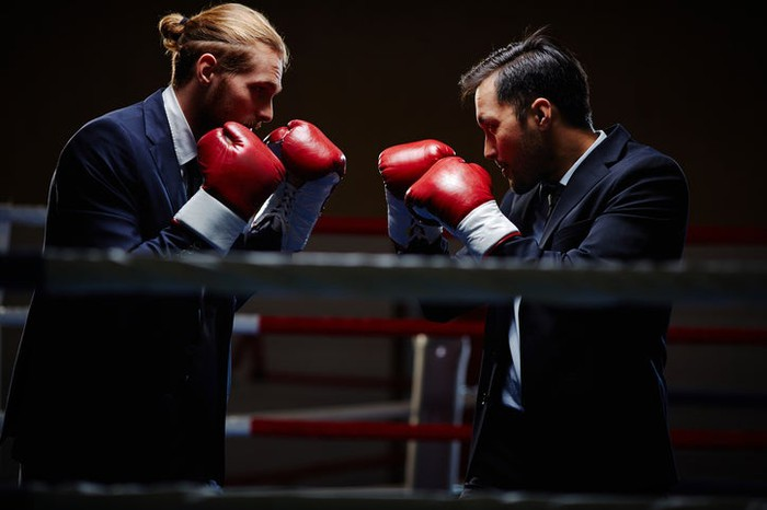 Two men in business suits facing each other in a boxing ring with their red gloved-fists up.