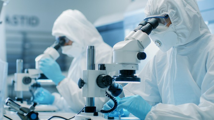 Two people in full-coverage lab suits looking through microscopes.