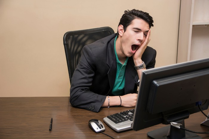 Man sitting at computer, holding his face while yawning