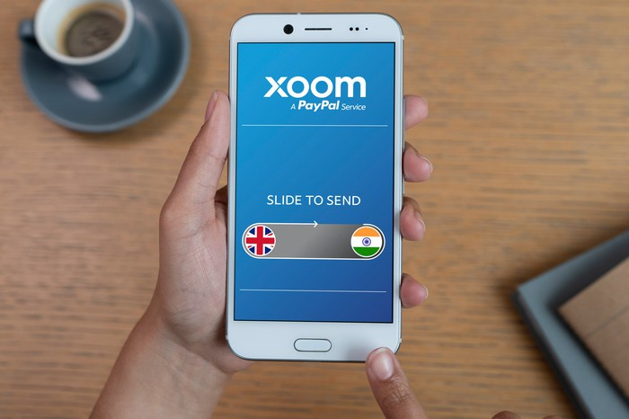A man holding a smartphone featuring the Xoom app.