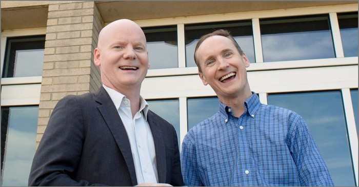 Two white men smiling at the camera with a window behind them. One is bald and wearing a dark sportcoat and a cream-colored shirt; they other has a receding hairline and is wearing a dark blue checkered shirt. You can see blue sky and clouds reflected in the windows.