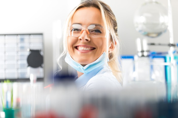 A woman in a lab coat in a lab smiling.