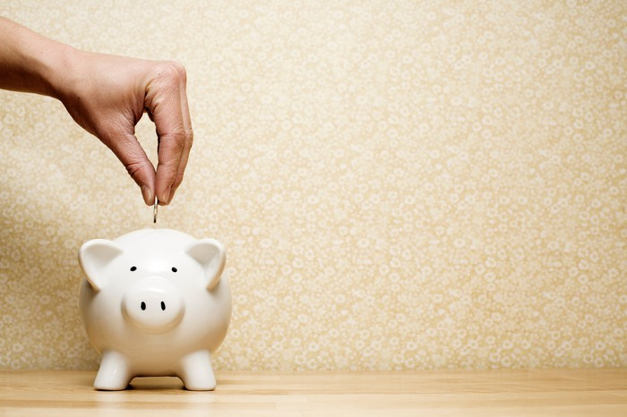 Hand putting coin into a piggy bank.