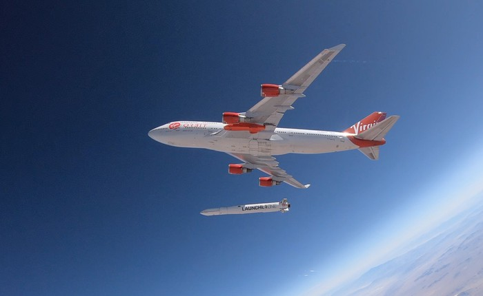Red and white Cosmic Girl airplane dropping red and white LauncherOne rocket from midair