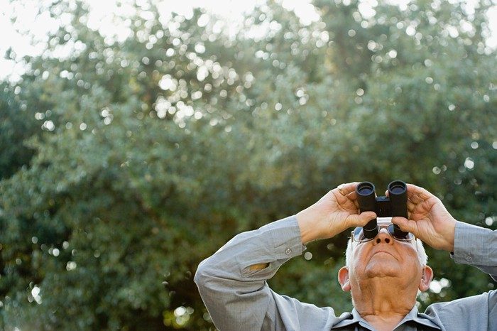 A senior man looks up at the sky through binoculars.