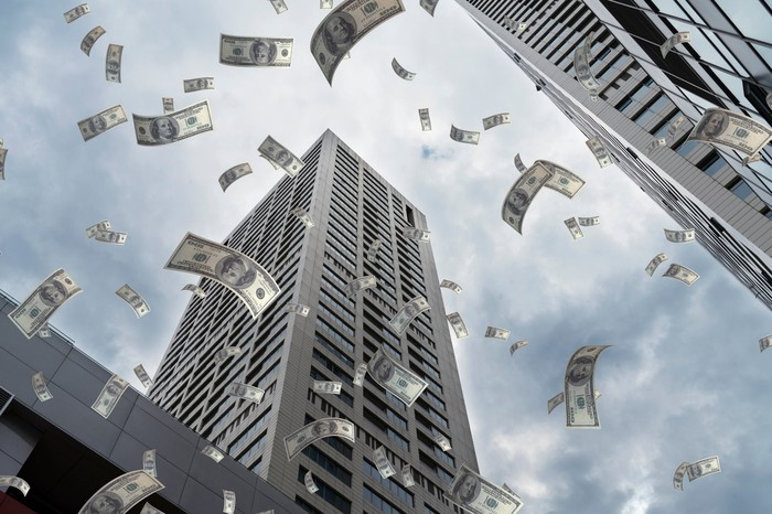 Dollars falling from the sky amid tall buildings.