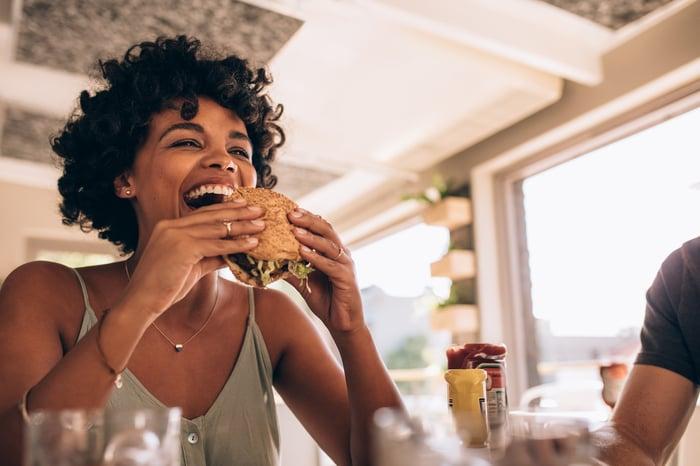 Femme appréciant de manger un hamburger au restaurant