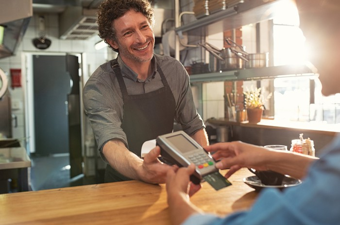 A smiling male barista holds out a card reader to a customer.