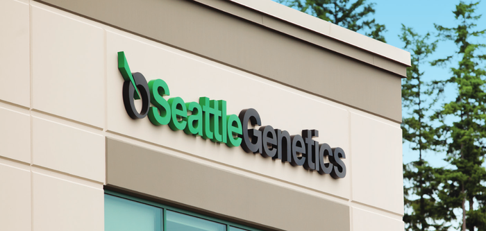 Seattle Genetics logo on side of building with trees nearby.